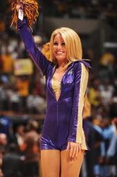 Laker Girl Whitney in a tight purple outfit waves a pom pom.jpg