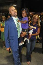 Derek Fisher and his wife Candace carry their daughters.jpg