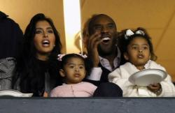 Vanessa and Kobe Bryant watch a game with their daughters.jpg