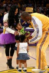 Vanessa Bryant and her daughters hand Kobe a flower bouquet.jpg