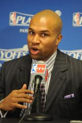 Derek Fisher in a striped suit speaks to the media.jpg