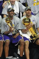 Kobe Bryant holding NBA Finals MVP trophy while Derek Fisher holds the Championship trophy.jpg