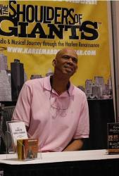 Kareem sits at a booth for The Shoulders of Giants.jpg