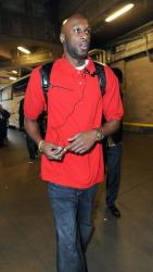 Lamar Odom in a red shirt and jeans.jpg