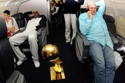 Sun Yue sits next to Kobe Bryant and Phil Jackson on the phone on plane.jpg