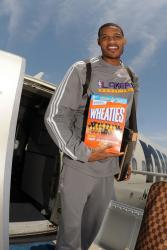 Trevor Ariza holds the Lakers 2009 Champions Wheaties box as he gets out of the plane.jpg
