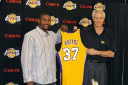 Ron Artest hold up his new Lakers jersey with Mitch Kupchak.jpg