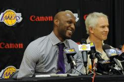 Lamar Odom in gray striped shirt and purple tie smiles next to Mictch Kupchak.jpg