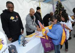 Josh Powell and Derek Fisher and other Lakers hand out Laker pennants.JPG