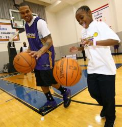 Shannon Brown instructs a young fan at a clinic.JPG