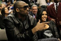 Vanessa Bryant smiles as Kobe looks on in a black jacket during the 2010 NBA All Star events.JPG