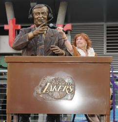 Marge Hearn holds up a microphone to Chick Hearn's statue.JPG