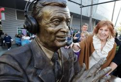 Marge Hearn smiles and puts her hand on the shoulder of Chick Hearn's statue.JPG