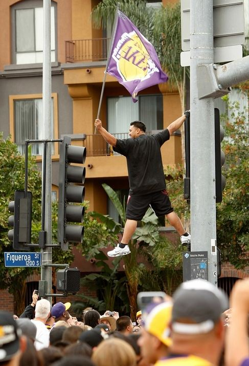 7e3c8a454fc Laker fan climbs on a traffic pole raising a Laker flag at Figueroa St  during the Lakers Championship Parade 2010.