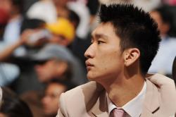 Sun Yue looks on from the sidelines in a suit.jpg