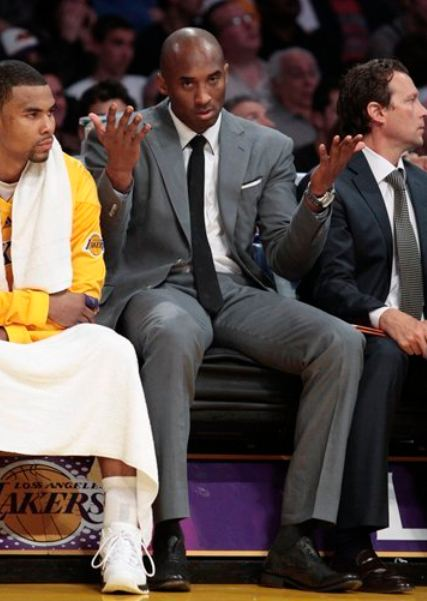 Kobe Bryant Stares And Raises Both Hands While In A Suit On