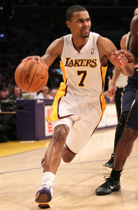 Ramon Sessions dribbles the ball in a Laker white home jersey.JPG