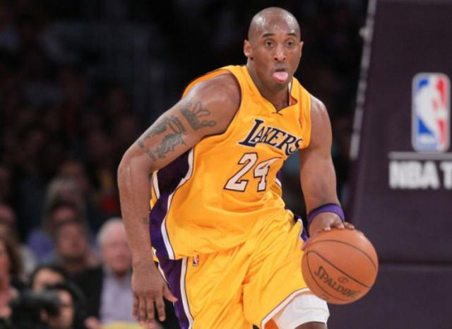 Kobe Bryant in Laker gold jersey sticks out his tongue as he pushes the ball upcourt.JPG