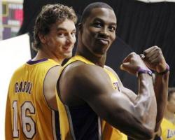 Dwight Howard Ironman flexes his muscles in a Laker jersey next to Pau Gasol.JPG