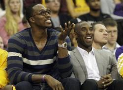 Dwight Howard in street clothes next to Kobe Bryant sitting on the bench smiling.JPG