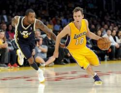 Steve Nash in a Laker uniform drives past Mo Williams.JPG