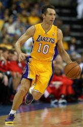 Steve Nash dashes up court dribbling the ball in a Laker home jersey.JPG