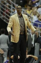 Dwight Howard stands and looks on in a beige jacket and plaid shirt.JPG