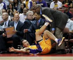 Steve Nash falls into the sideline next to coach Mike Brown.JPG