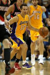 Steve Nash tongue out dribbles the ball with Pau Gasol trailing.JPG