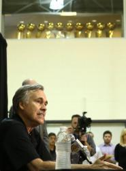 Mike D'Antoni speaks during his introduction press conference with Laker championship trophies above him on next to a window.JPG