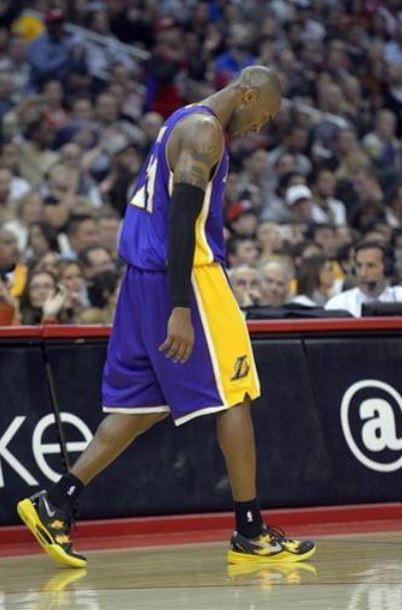Kobe Bryant walks away head down in a Laker road jersey JPG