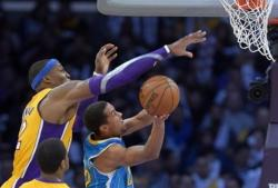 Dwight Howard looks to block Brian Roberts' shot.JPG