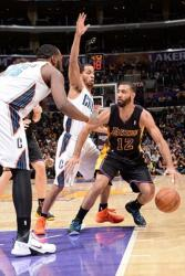 Kendall Marshall in black Laker jersey sees 2 Bobcats in the paint.JPG