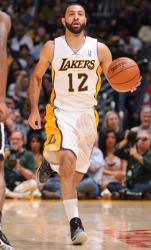 Kendall Marshall brings the ball upcourt in white Lakers jersey.JPG