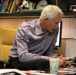 Mitch Kupchak sits at his desk looking on.JPG