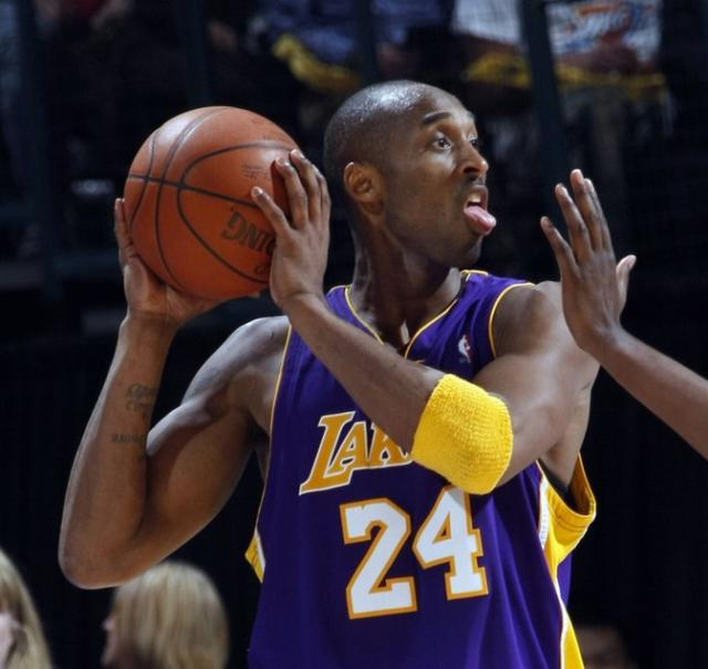 kobe bryant sticks out his tongue while holding the basketball jpg